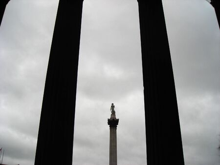 invincible: View of the Nelson statue at Trafalgar Square between the entrance columns of the National Gallery Stock Photo
