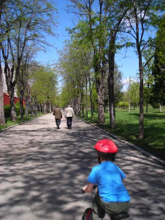 A boy chasing his grandfather on a bicycle.