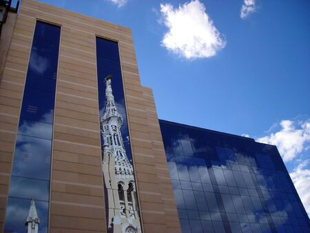 Reflection of a church tower on an office building on a sunny afternoon in Madrid. Stock Photo