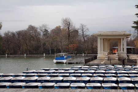 Rowing boats for hiring out on the lake of Retiro Gardens in a cloudy  winter morning in Madrid.