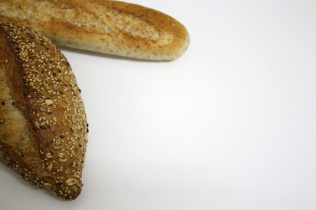 A french baguette and a german bread isolated on a white background, copy space available. Stock Photo