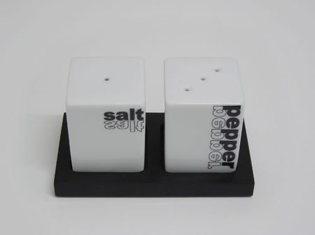 Frontal view of a black and white saltcellar and peppershaker .