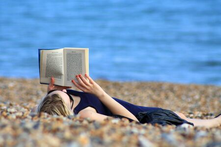 A girl reading a book on the beach.