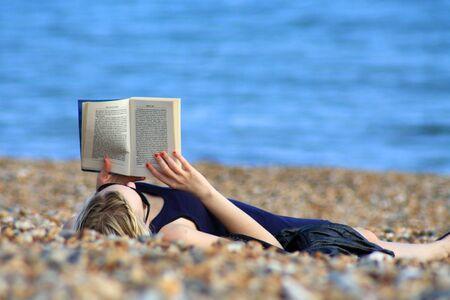 一个女孩在海滩上看书。
