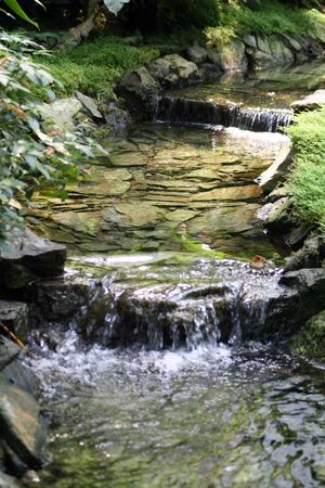 Water running among small waterfalls in a man-made stream. Stock Photo