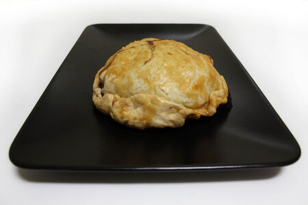 Pork Pie served on a black plate, ready to eat.