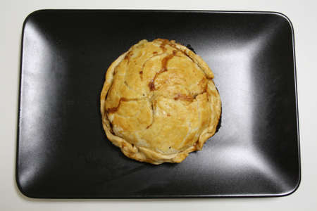 High angle view of a Pork Pie on a plate. Stock Photo