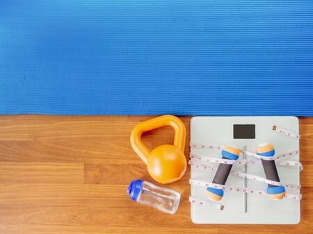 weight loss and physical activity concept from weight scale digital with measure tape for check body shape and workout equipment on a wooden floor.