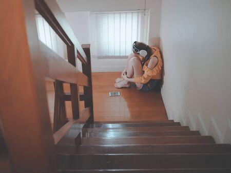 Concept d'amour de coeur brisé d'Emotion sentant une jeune fille asiatique triste en écoutant de la musique assise dans les escaliers à l'intérieur de la maison. zoné à la musique.