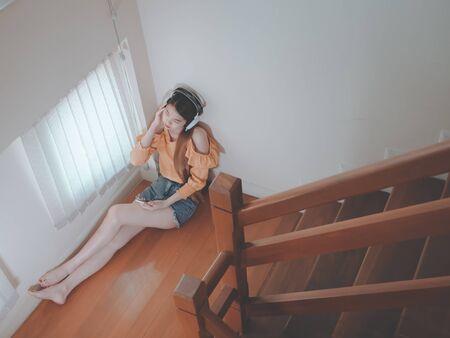 Concept d'amour de coeur brisé d'Emotion sentant une jeune fille asiatique triste en écoutant de la musique assise dans les escaliers à l'intérieur de la maison. zoné à la musique. Banque d'images