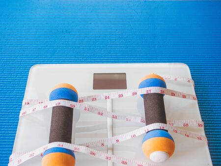 weight loss and physical activity concept from weight scale digital with measure tape for check body shape and workout equipment on yoga mat