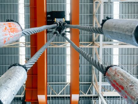 Overhead crane and machine inside factory building, industrial background.