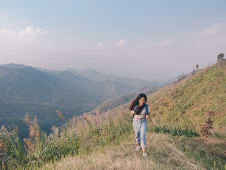 wanderlust and travel concept from Happy asian young woman walking trail in mountain with amazing view. Trekking mountain on National park in Thailand.