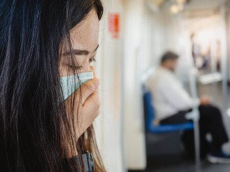 asian woman wearing protective mask against virus and air pollution in public transport.