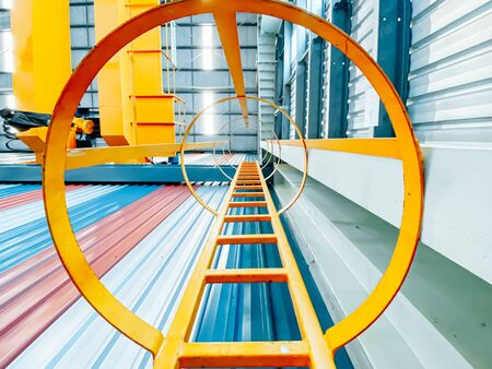 Overhead crane and fixed ladder inside factory building, industrial background