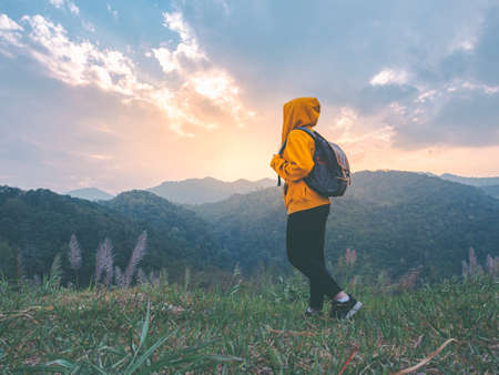 woman hiking with backpack relaxing in nature and enjoy the sunset view on mountain peak at Mae Wong national park Thailand.