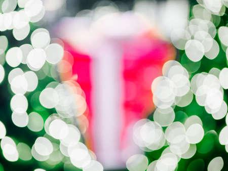 Abstract blur of night bokeh light on Christmas tree with big gift box. Stock Photo