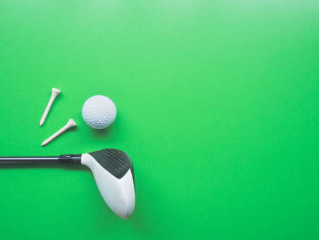 Golf equipment flat lay on green background. Top view