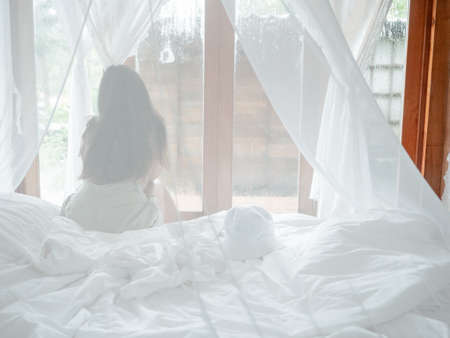 Back view of woman relaxing sitting on bed in mosquito net of an hotel room looking through window in vacations