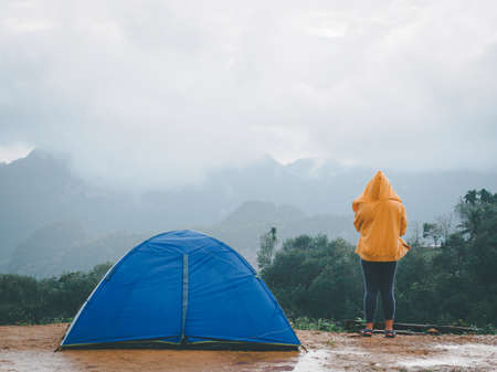 Woman camping blue tent on mountain peak and enjoying beautiful nature of hills and during rainy season at Doi Tapang, Sawi District, Chumphon, Thailand.