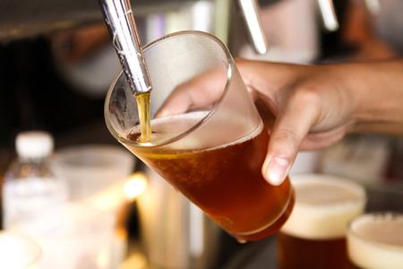 grifos: grifo de cerveza que vierte una cerveza de barril Foto de archivo