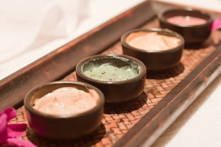 mud-mask, scrub creme,massage oil surrounded by petals photo