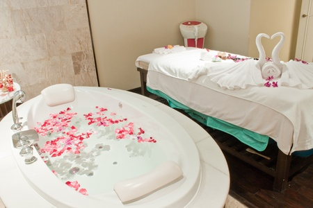 Spa  with bath  surrounded by rose petals