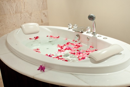 Spa  with bath  surrounded by rose petals photo