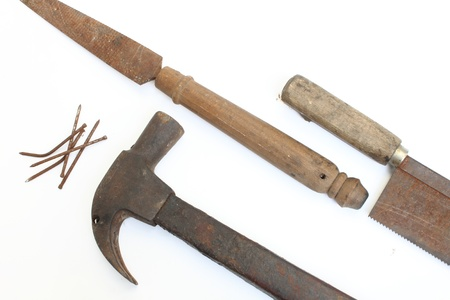 Old carpentry tools, tack saws, hammers and metal hone. photo