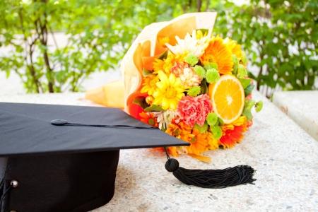 Maturitní čepice a krásná květina Reklamní fotografie