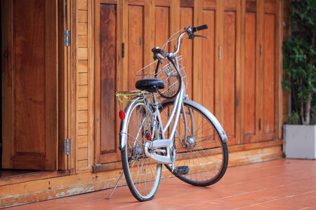 Old bicycle on vintage wooden house wall photo