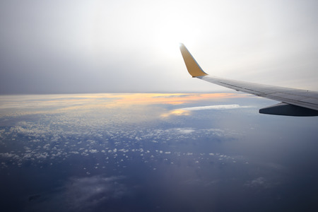 Wing of an airplane flying above the  clouds and sky as seen through window of an aircraft