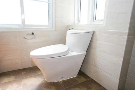 white flush toilet  in a building interior Stock Photo