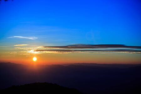 Beautiful Mountain and sunrise silhouette of mountains on yellow  background Stock Photo