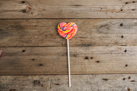 candy canes as heart on wooden board