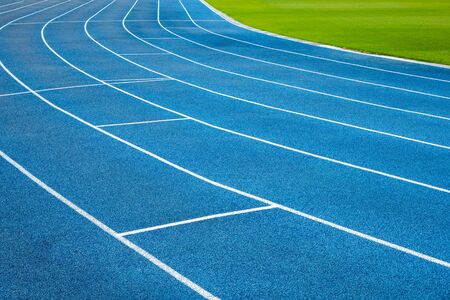 Blue running treadmill track with lane numbers in stadium outdoors.Starting grid of race track at the stadium