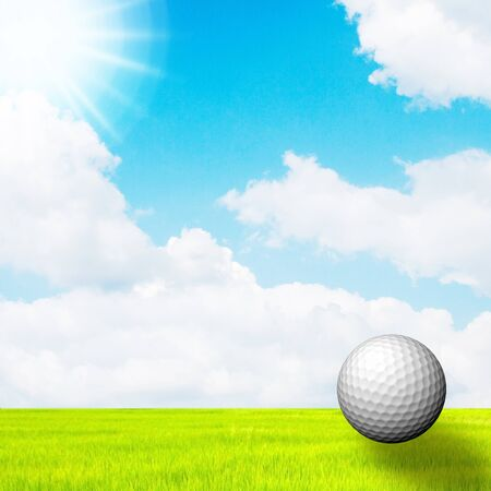 golf ball in green grass on a blue sky and sun photo