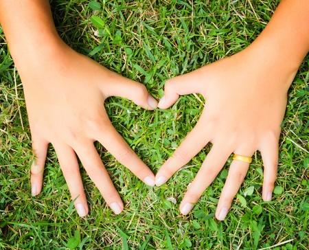 hacer el amor: Las manos de una pareja de enamorados dar forma a un corazón