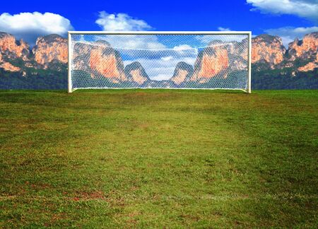 field goal: soccerball goal in soccer field on Mountain and sky