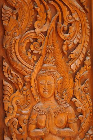 The angels are carved in the door of the temple of Wat Thai photo