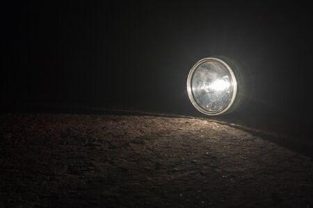 Flashlight falling on the road at night.