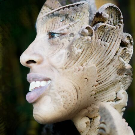 Double exposure profile portrait of young smiling female traveller combined with close up of a rock sculpture from a Balinese temple in southeast asia 写真素材