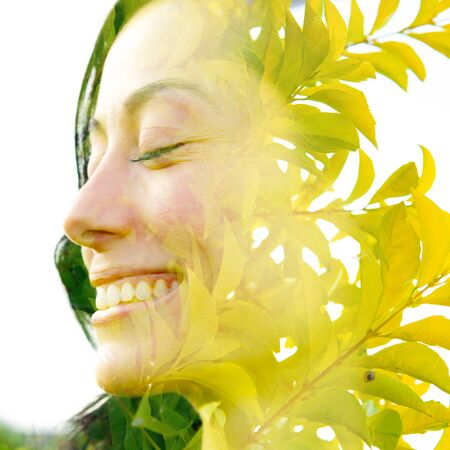 Double exposure profile portrait of a young, relaxed natural beauty with closed eyes and a big smile combined with bright green tropical leaves in a peaceful setting