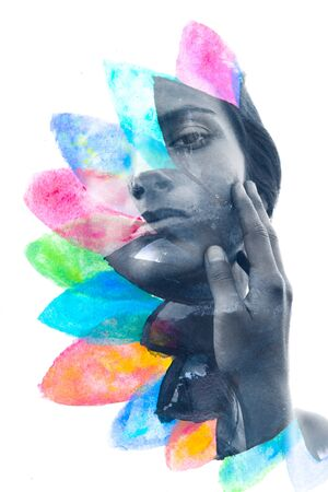 Paintography. Double exposure portrait of a young woman disappearing behind handmade painting of colorful petal like shapes