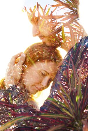 Double exposure of a couple with melancholic sad expression dissolving behind tropical plants Reklamní fotografie