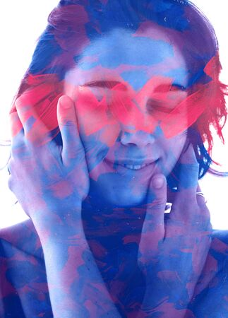 Paintography. Double exposure portrait of woman with short hair and hands gently on face, combined with hand painted blue and pink brush strokes