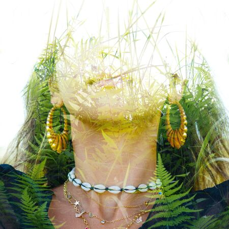 Double exposure of a young healthy female looking straight into the camera pulling her hair back, combined with bright green tropical leaves