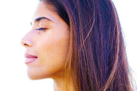 Profielportret van jonge vrouw met vlekkeloze huid, op witte achtergrond