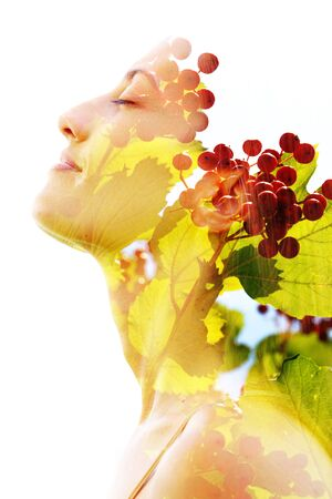 Double exposure portrait of bright green leaves and red fruits combined with a peaceful womans face with closed eyes 版權商用圖片