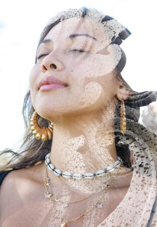 Double exposure profile portrait of young female traveller combined with close up of a rock sculpture from a Balinese temple in southeast asia